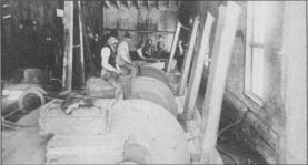Workers sit astride their grinding wheels in this photo from the Rockford (III.) Cutlery Co., taken about 1900.