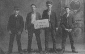"Holding a sign stating ""We're Printers, by gravy,"" these young men had their photograph taken in the mid-1890s, possibly to commemorate the end of their apprenticeships. (From the collections of Henry Ford Museum & Greenfield Village.)"