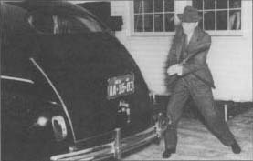 Henry Ford demonstrates the durability of automobile components made from saybeans by striking the trunk of a car with an axe. (From the collections of Henry Ford Museum & Greenfield village.)